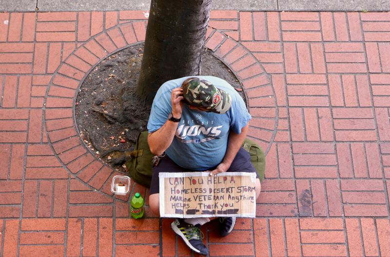 TRIBUNE PHOTO: ZANE SPARLING - A person sitting in downtown Portland holds a sign asking for help as a homeless veteran.