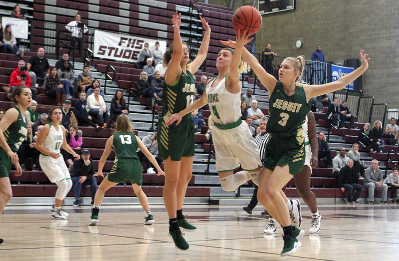 TIDINGS PHOTO: MILES VANCE - West Linn's Audrey Roden splits two Jesuit defenders for a shot during her team's 60-51 win in the third round of the PIL Holiday Classic at Franklin High School on Saturday.