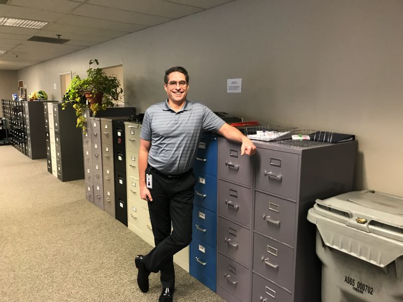 TRIBUNE PHOTO: SHASTA KEARNS MOORE - Gresham-Barlow School District Executive Director of Student Support Services John Koch stands next to file cabinets filled with student files. The files have now been digitized.