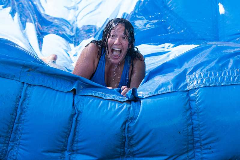 STAFF PHOTO: CHRISTOPHER OERTELL - Jen Winklepleck slides down a water slide during a break in a massive water balloon fight at Shute Park on Aug. 4.