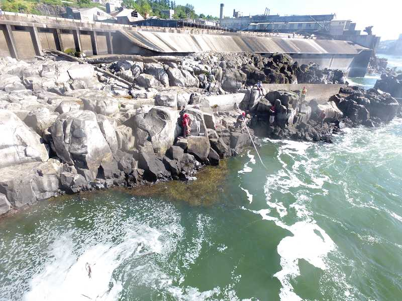 Amid pushback from multiple parties, the Confederated Tribes of Grand Ronde completed a new fishing platform at Willamette Falls. Previously, fishers had to balance on the rocks, as shown here.