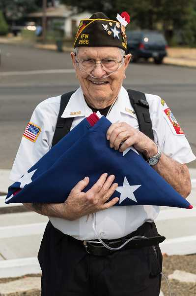 STAFF PHOTO: CHRISTOPHER OERTELL - Ellsworth 'Pa' Bell, a World War II veteran from Rock Creek, holds up Revolutionary War replica flag in August.