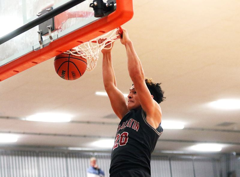 TIMES PHOTO: DAN BROOD - Tualatin High School junior John Miller goes up high for a dunk during the Timberwolves 73-57 win at Beaverton on Friday.