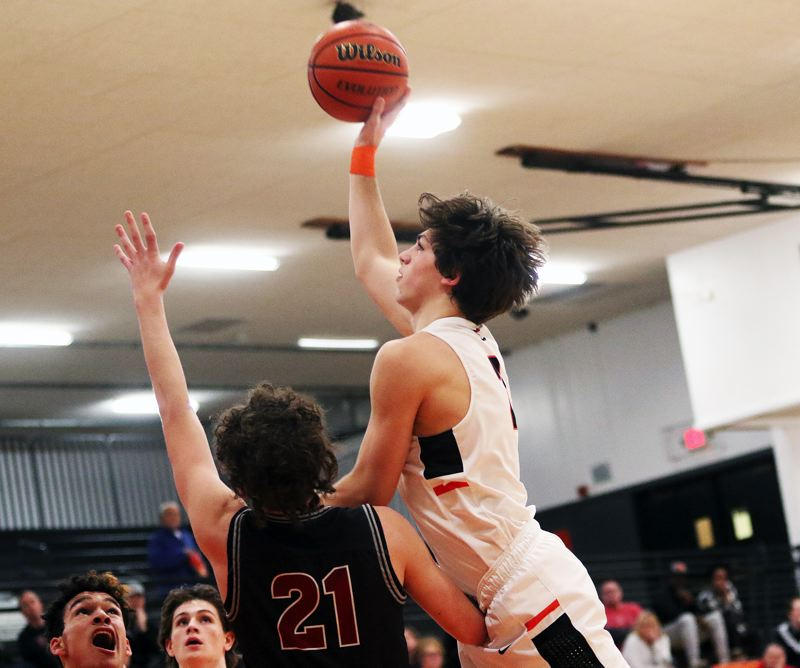 TIMES PHOTO: DAN BROOD - Beaverton junior Bennett Giebels shoots over Tualatin sophomore Logan Shaw during Fridays game. The Wolves got a 73-57 victory.