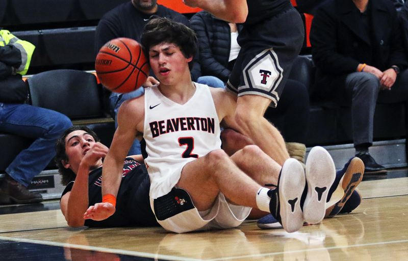 TIMES PHOTO: DAN BROOD - Tualatin senior Bridger Steppe (left) throws the ball off of Beaverton junior Bennett Giebels head near the end line during Fridays game.