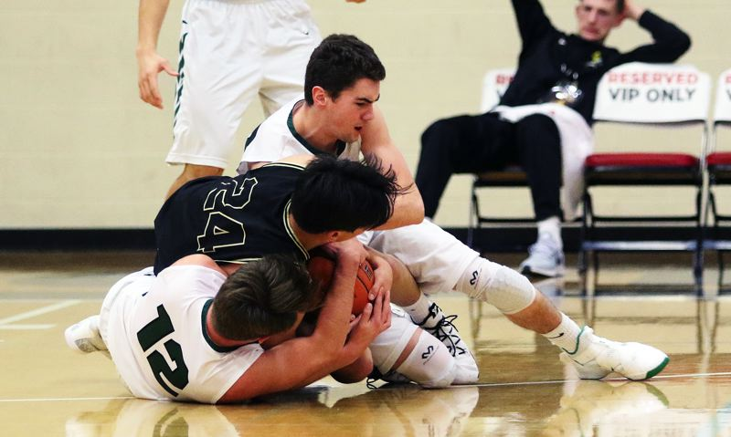 TIMES PHOTO: DAN BROOD - Tigard seniors Carson Crist (12) and Luke Ness battle Southridge senior Pono Van Dusen for the ball during Fridays game at the Les Schwab Invitational.