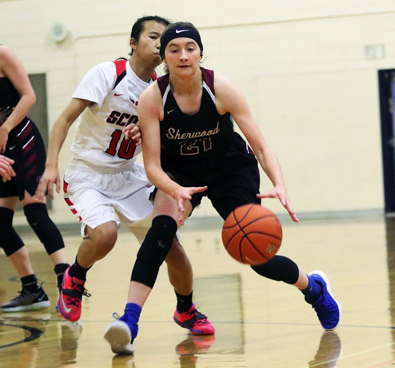 TIMES PHOTO: DAN BROOD - Sherwood junior Ava Boughey goes for a loose ball in front of David Douglas sophomore Ziling Zhen.