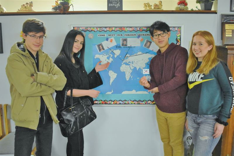 ESTACADA NEWS PHOTO: EMILY LINDSTRAND - Estacada High School foreign exchange students Emery Ago, Angel Dorinet, Jung Su Park and Kat Hoeye point to their home countries on a map at the schools front office.