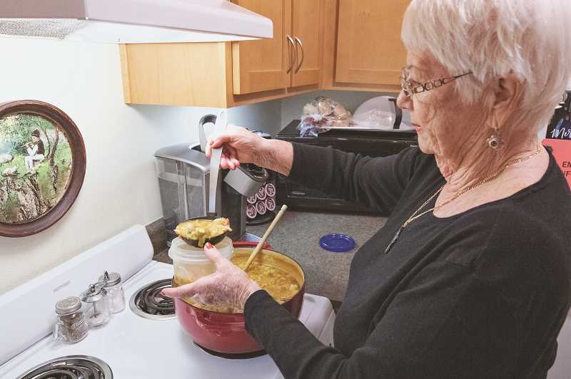 SPOKESMAN PHOTO: JONATHAN HOUSE - Jean Hornsby pours out portions of her chicken and vegetable soup that she then delivers.