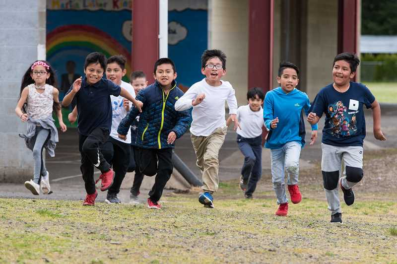 STAFF PHOTO: CHRISTOPHER OERTELL - Third- and fourth-graders run around the school grounds at Cornelius Elementary School on May 1.