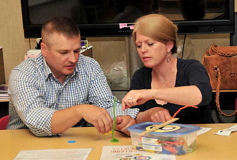 SPOKESMAN PHOTO: VERN UYETAKE - Parents Judy and Andy Foltz work on a challenge during Wood Primarys  back to school night in September.