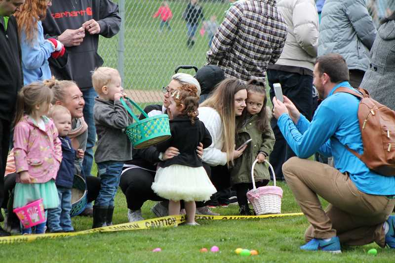SPOKESMAN PHOTO LESLIE PUGMIRE HOLE - Kyle Stanfield  of Wilsonville captures the moment for his wife Kelly and Grant, age 2 and Chase, age 1, during the March 31 Easter Egg hunt in Memorial Park.