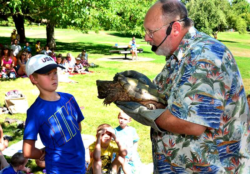 SPOKESMAN PHOTO VERN UYETAKE -  Reptile man Rich Richey gives Levi Ryan of Wilsonville an up close and personal look at a snapping turtle at a summer event sponsored by the Wilsonville Library at Murase Plaza.