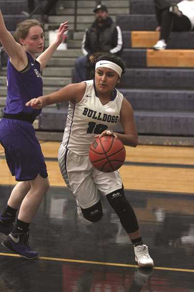 PHIL HAWKINS - Woodburn junior Lina Cabrera drives around a Blanchet defender in the Bulldogs' 71-32 loss in the opening round of the Stayton Holiday Classic.