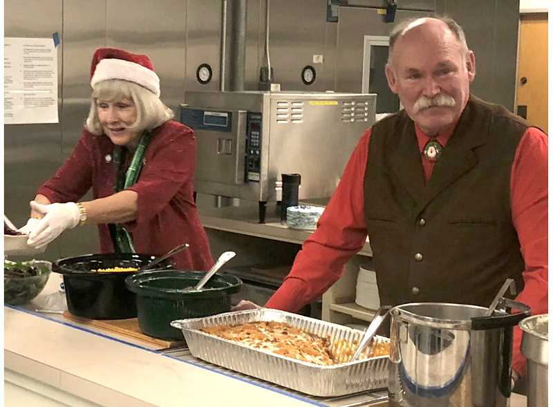PHOTO BY JOHN STEVENS - Jefferson County Commissioner Mae Huston and Jim Rahi serve dinner to veterans and their families on Dec. 24, at the Jefferson County Senior Center.