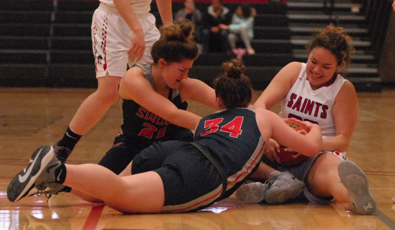 OUTLOOK PHOTO: DAVID BALL - Mt. Hood CCs Bri Rosales wrestles a pair of SW Oregon players to tie up a loose ball during the Saints 70-69 home win Wednesday.