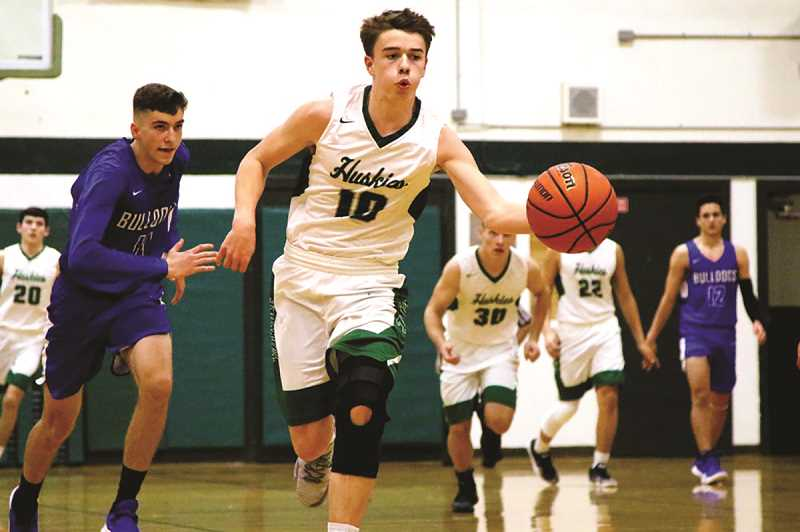JO WHEAT - North Marion senior guard Jared Hauser had eight points, seven assists, five rebounds and two steals in the Huskies' 95-82 win over Woodburn on Dec. 22. It was the second time the two teams have played this season, the first won by the Bulldogs 82-63 on Nov. 30.