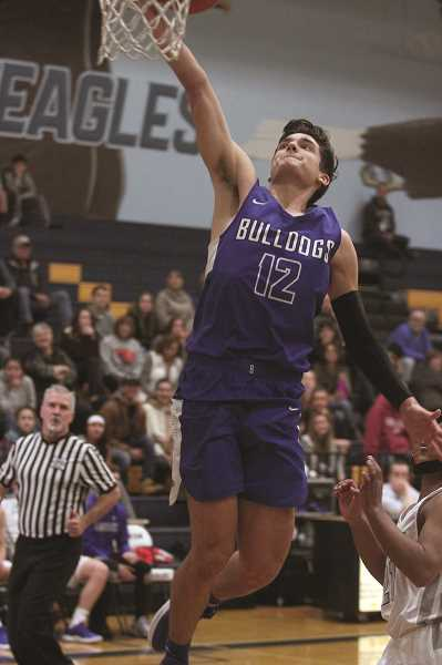 PHIL HAWKINS - Woodburn senior R.J. Veliz rises up for a dunk attempt in the Bulldogs' 88-49 victory over the Blanchet Catholic Cavaliers on Thursday.