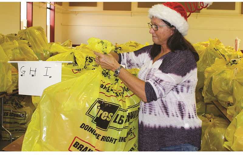 HOLLY SCHOLZ/CENTRAL OREGONIAN  - Holiday Partnership Co-Coordinator Vicky Ryan prepares one of the hundreds of gift bags distributed during the Holiday Partnership.