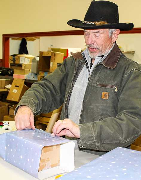 HOLLY SCHOLZ/CENTRAL OREGONIAN  - Volunteer Richard Rath wraps gifts that would later go to children in need.