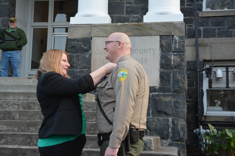 SPOTLIGHT PHOTO: COURTNEY VAUGHN - Annette Pixley pins a sheriffs badge on her husband, Brian Pixley, shortly after he is sworn in for his first term as sheriff Wednesday, Jan. 2.