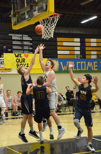 PHOTO COURTESY: JOHN BREWINGTON - St. Helens High post Parker Miller battles inside against Hood River Valley for two of his 19 points in the Lions' 64-45 home-court victory.