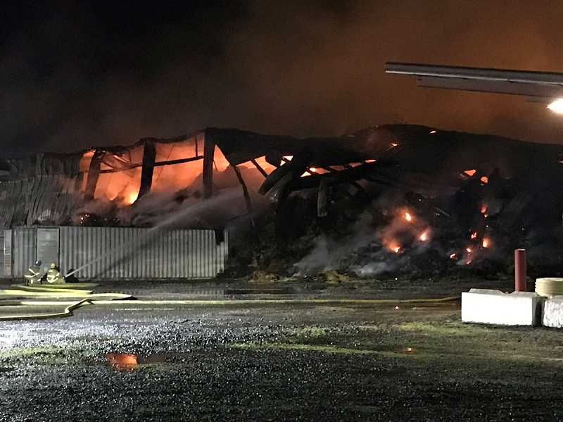 COURTESY OF AURORA FIRE DISTRICT - Firefighters from multiple districts battle a blaze at Anderson Hay & Grain Company near Aurora on Wednesday, Jan. 2.