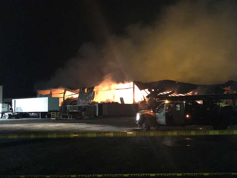 KRISTEN WOHLERS - Anderson Hay and Grain Co. hay warehouse glows on the night of Jan. 3 as the building begins to collapse.