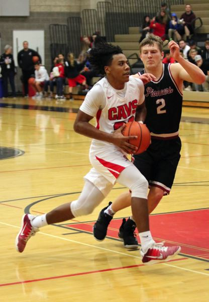 PAMPLIN MEDIA: JIM BESEDA - Clackamas' Jailen Hammer powers his way past Sandy's Colby Carson as he drives to the basket in the first half of Friday's Mt. Hood Conference opener at Clackamas.