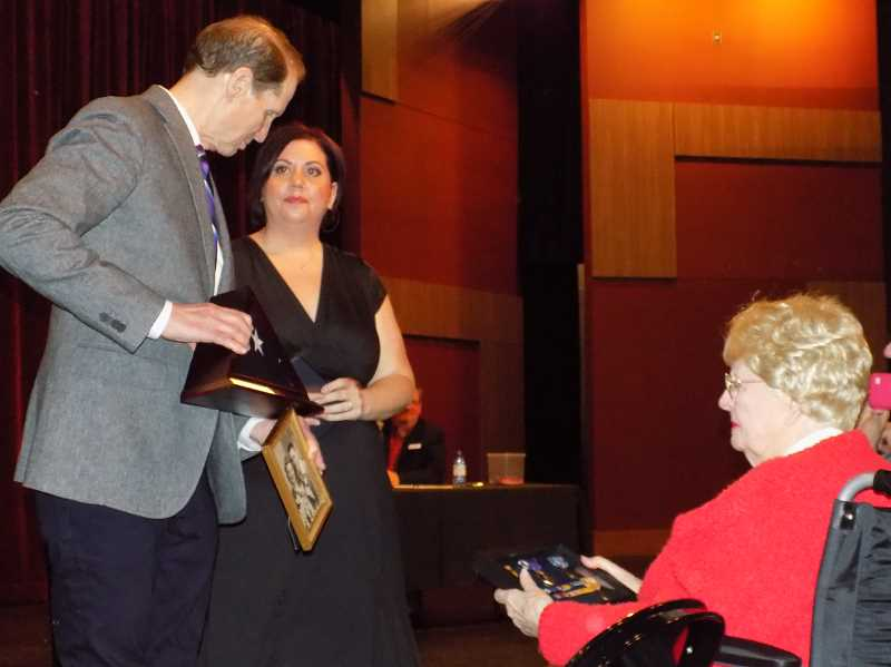 TIMES PHOTO: RAY PITZ - U.S. Sen. Ron Wyden, left, presents an American flag, along with a variety of medals to Aimee Heath, middle, the granddaughter of June Close, right. Close was married to Vernon Garner, a World War II sailor who was killed aboard the USS Pensacola during World War II. She subsequently married Garner's best friend, James Close Sr.
