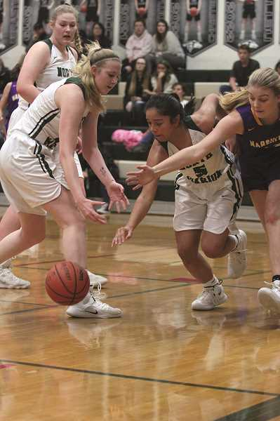 PHIL HAWKINS - North Marion seniors Paige Martin and Mar Verastegui poke a Marshfield pass loose in the second quarter of the Huskies 46-31 win over the No. 1 Pirates on Thursday.