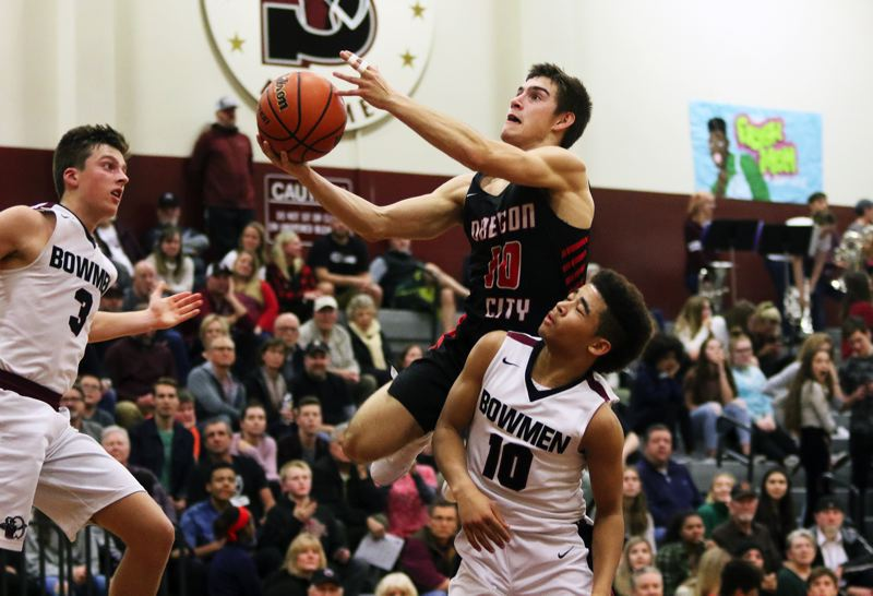 TIMES PHOTO: DAN BROOD - Oregon City senior Corban Remsburg looks to go up to the basket between Sherwood senior Tyler Hix (left) and junior Jamison Guerra during Friday's game.