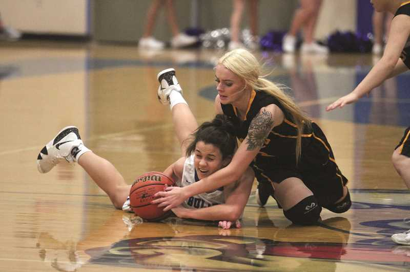 PHIL HAWKINS - Woodburn freshman Aria Kent wrestles for a loose ball with Sweet Home senior Shahalie Erickson.