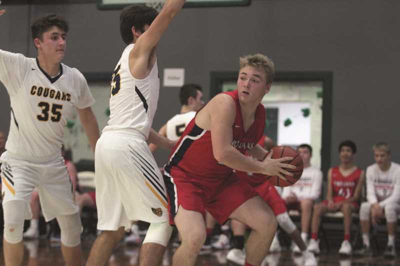 PHIL HAWKINS - Kennedy senior Carson Hall looks to find an open teammate out of the post against Portland Adventist.