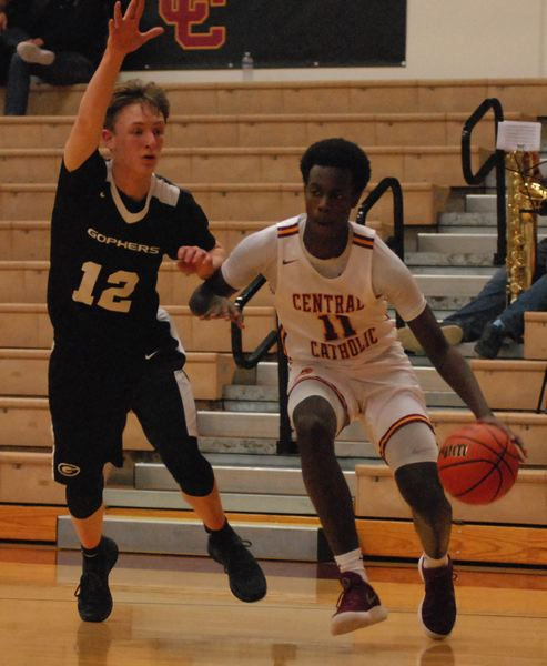 OUTLOOK PHOTO: DAVID BALL - Central Catholic's Darius Gakwasi dribbles out of the corner against Gresham defender Ethan Abrahamson during the Rams' 76-54 home win Friday.
