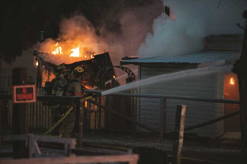 LON AUSTIN - Firefighters work to extinguish fire at the Melrose Drive home.