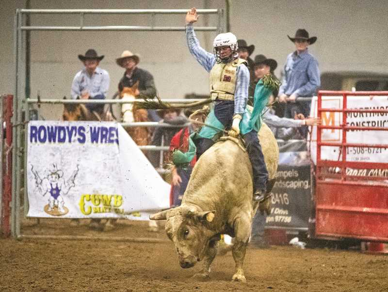 LON AUSTIN/CENTRAL OREGONIAN  - Prineville cowboy Mason Cooley rides a bull during the Buckin' for Rowdy bull-riding benefit event Dec. 29.