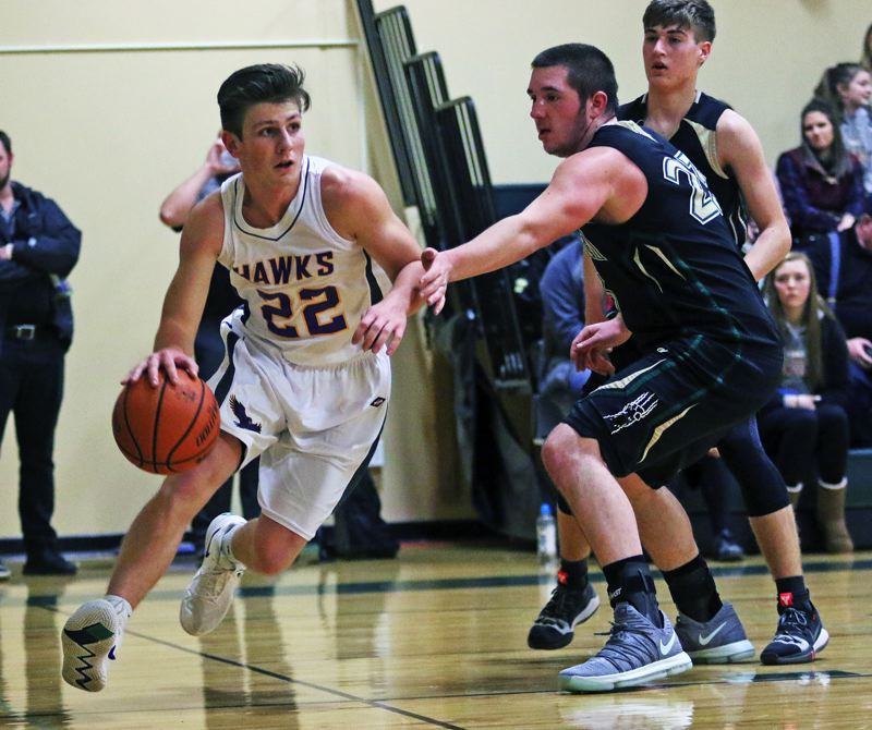 TIMES PHOTO: DAN BROOD - Horizon Christian senior Travis Schiele (left) looks to drive past Gold Beach senior Jonny Moore during the Hawks 71-42 victory.