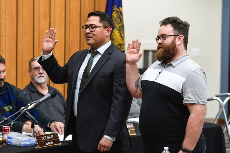 STAFF PHOTO: CHRISTOPHER OERTELL - Luis Hernandez, center, and John Colgan, right, raise their right hands as they are sworn in as Cornelius city councilors on Monday, Jan. 7.
