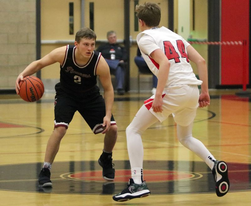 PAMPLIN MEDIA: JIM BESEDA - Sandy guard Colby Carson sizes up Clackamas defender Damon Erickson on his way over halfcourt during the Pioneers 77-63 road loss last Friday.
