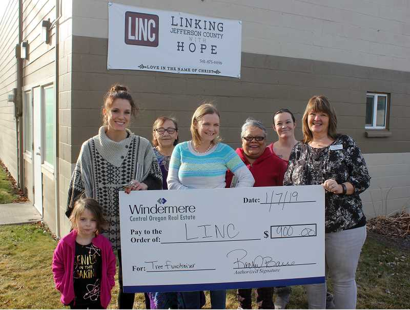 DESIREE BERGSTRON/MADRAS PIONEER - Pictured at the check presentation are, from left, Glenna Bare and mom Rachel Bare, Madras Windermere broker, LINC staff Penny Medrano, director Austin Cooper, Juanita Chavez, Mellody Barnes, and Windermere broker Amy Brown.