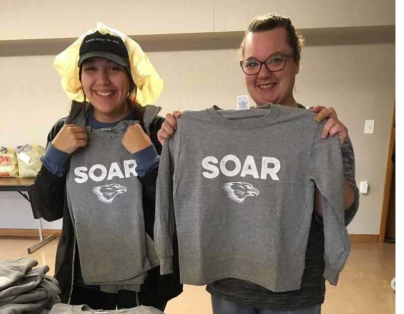 SUBMITTED PHOTO - LINC volunteers show some of the 630 T-shirts that were given to W.S. students.