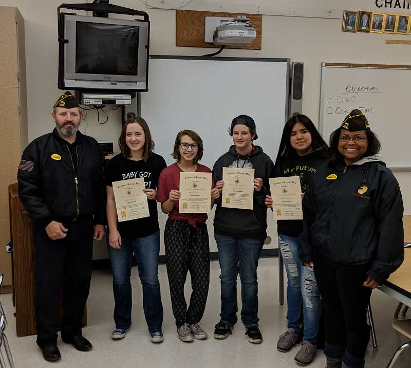 SUBMITTED PHOTO - VFW Commander Duane Ledford, left, gives certificates to MHS students Riley Russell, second from left, Alyssa Collver, Ryane Dobkins, and Amy Melgarejo, with Cecilia Ledford on far right.