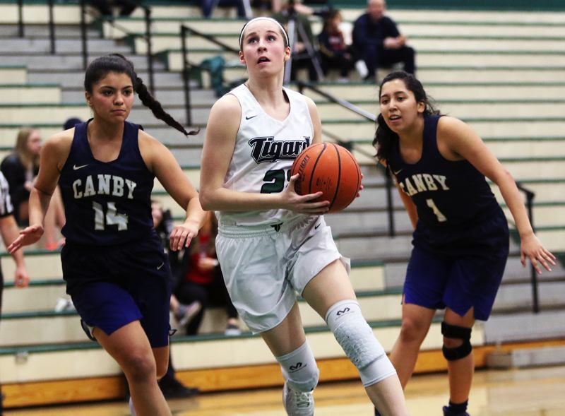 TIMES PHOTO: DAN BROOD - Tigard High School junior Delaney Leavitt looks to go to the basket between Canbysenior Aracely Barjas (left) and Naaral Gomez during Tuesdays game.