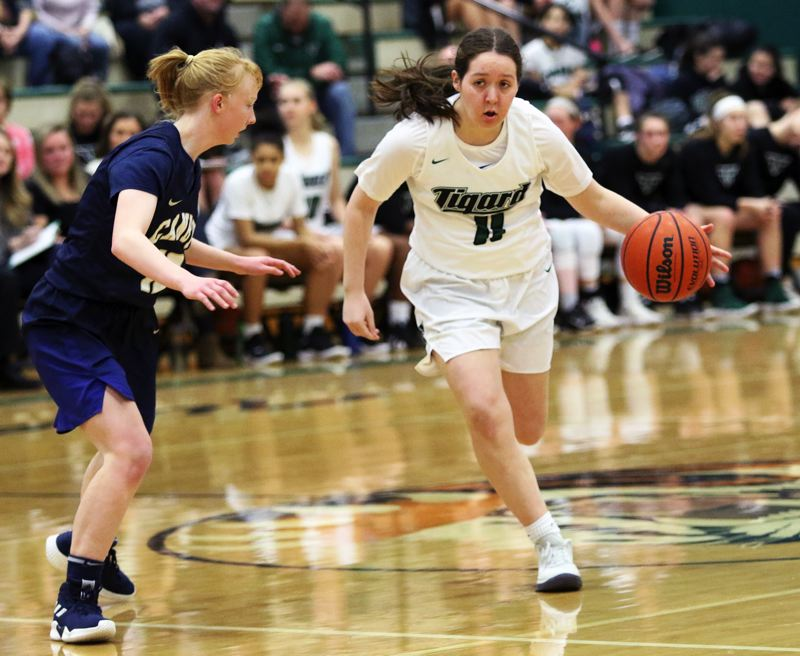 TIMES PHOTO: DAN BROOD - Tigard High School senior Paige LaFountain (right) brings the ball into front court against Canby sophomore Zoe Thompson during Tuesdays game.