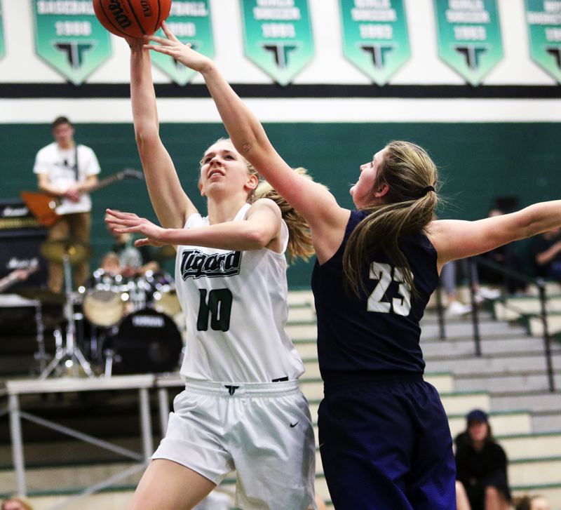TIMES PHOTO: DAN BROOD - Tigard freshman Sarah Lamet (left) goes up to the basket against Canby's Nicole Mickelson during Tuesday's game.