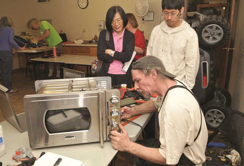 REVIEW FILE PHOTO: VERN UYETAKE - George Denison of Lake Oswego works on a microwave oven during last year's Repair Fair in Lake Oswego.