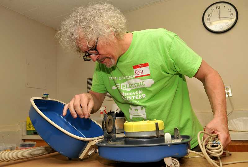 REVIEW FILE PHOTO: VERN UYETAKE - Kevin Bryck of West Linn does his best to fix a vacuum cleaner during Lake Oswego's first Repair Fair in 2018.