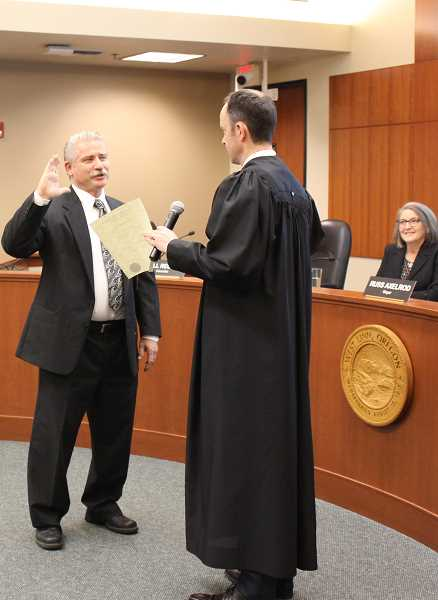 Bill Relyea raises his right hand as he's sworn into office as a city councilor.