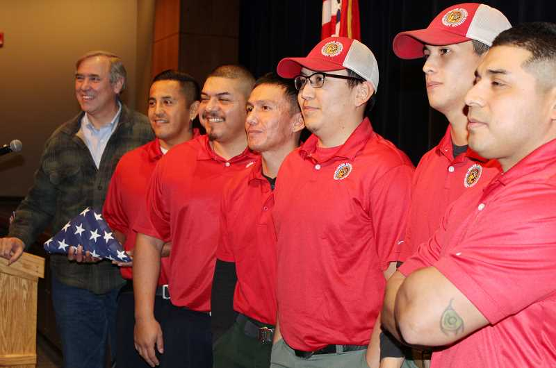 HOLLY M. GILL/MADRAS PIONEER - U.S. Sen. Jeff Merkley, left, presents the Warm Springs Hotshots team with a U.S. flag at the start of a town hall at the Madras Performing Arts Center on Friday, Jan. 4. The Warm Springs Fire Management's Hotshots, from left to right include Superintendent Gary Sampson, Capt. Renso.Rodriguez, Stephen Vaeth, Rodney Mitchell, Hiram Yaw and Dabid Rodriguez.